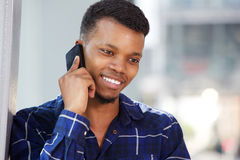 Handsome young man talking on mobile phone smiling Stock Images