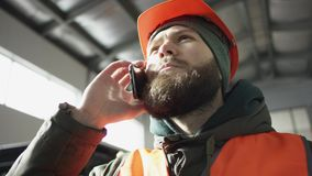 Handsome young man talking on the mobile phone and smiling while standing in workshop with car in the background. Mechanic. He keeps equipment available for use stock footage