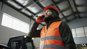 Handsome young man talking on the mobile phone and smiling while standing in workshop with car in the background stock footage