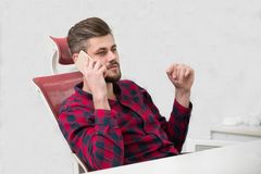 Handsome young man talking on phone while doing paperwork at workplace.  Royalty Free Stock Images