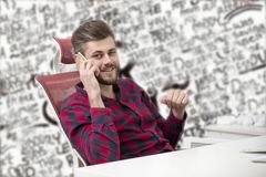 Handsome young man talking on phone while doing paperwork at workplace.  Royalty Free Stock Image