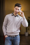 Handsome young man talking on the phone at home Stock Photography