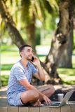 Handsome young man talking on phone while sitting on bench in park royalty free stock image