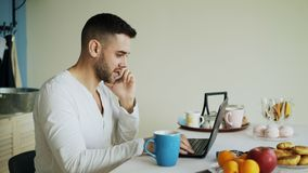 Handsome young man talking phone and using laptop computer sitting in the kitchen after breakfast in the morning Stock Photography
