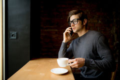 Handsome young man talking on a phone at a window while drinking his cup of coffee in the morning Royalty Free Stock Photography