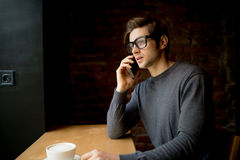 Handsome young man talking on a phone at a window while drinking his cup of coffee in the morning Royalty Free Stock Photo