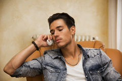 Handsome young man talking on telephone at home Royalty Free Stock Photography