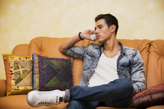 Handsome young man talking on telephone at home Stock Photography
