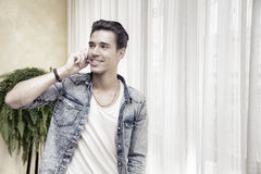 Handsome young man talking on telephone at home smiling Royalty Free Stock Images