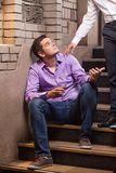 Handsome young man talking to man sitting on stairs. Stock Images