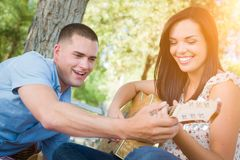 Handsome Young Man Teaching Mixed Race Girl to Play Guitar at th Royalty Free Stock Image