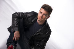 Handsome young man or teenager sitting on white floor. Wearing black leather jacket Royalty Free Stock Photo