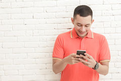 Handsome young man texting on mobilephone Stock Photography
