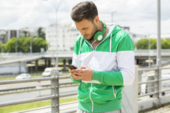Handsome young man texting outdoors Stock Image