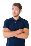 Handsome young man thinking with arms crossed Royalty Free Stock Images
