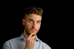 Handsome young man thinking, looking up Royalty Free Stock Photos