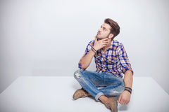 Handsome young man thinking while looking up. Stock Image
