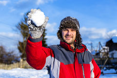 Handsome young man throwing a snowball Stock Photo