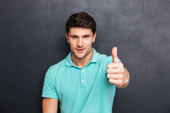 Handsome young man with thumb up looking at camera Stock Image
