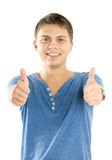 Handsome young man with thumbs up. On an isolated white background Stock Images