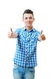 Handsome young man with thumbs up. On an isolated white background Royalty Free Stock Images