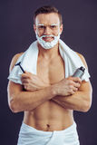 Handsome young man. Handsome man in towel with shaving foam on his face is smiling, holding a bottle of shaving foam and a razor, on a dark background Royalty Free Stock Photo