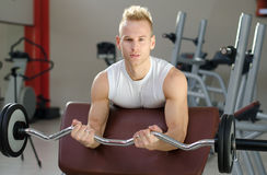 Handsome young man training biceps in gym Stock Photos