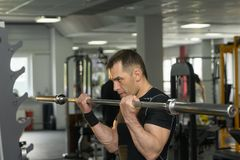 Handsome young man training biceps lifting barbell in a gym Royalty Free Stock Photos