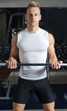 Handsome young man training biceps lifting barbell Stock Photos