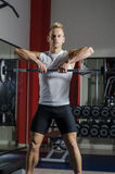 Handsome young man training shoulder lifting barbell Stock Photography