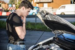 Handsome young man trying to repair a car engine Stock Photos