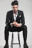 Handsome young man in tuxedo sitting on a stool Royalty Free Stock Images