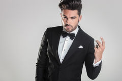Handsome young man in tuxedo snapping his finger Stock Photo