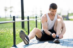 Handsome Young Man Tying Shoes Outdoors. Full length portrait of handsome young man tying sports shoes while sitting on running track in park, copy space royalty free stock photography