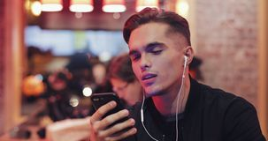 Handsome young man uses headphones and his smartphone for video call. He sits at the bar near the neon signs. Cheerful royalty free stock photography