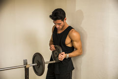 Handsome young man using barbell in gym Royalty Free Stock Image