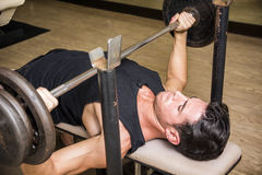 Handsome young man using barbell in gym Stock Images