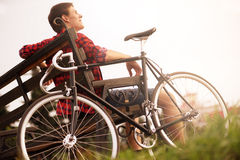 Handsome young man using cell phone by bicycle in Royalty Free Stock Photos