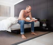 Handsome young man using a digital tablet in bedroom Stock Photography