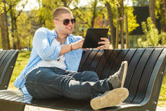 Handsome young man using digital tablet. Young man sitting in a park on a wooden bench and using digital tablet Royalty Free Stock Photography