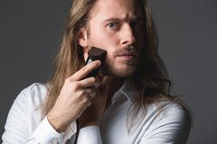 Handsome young man using electric razor. Looking good. Portrait of longhaired guy shaving his beard with shaver, looking concentrated. Isolated on grey Stock Photos