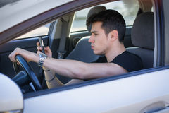 Handsome Young Man Using his Cell Phone Driving a. Inattentive Handsome Young Man Busy with his Mobile Phone While Driving a Car Royalty Free Stock Photography