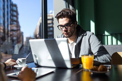 Handsome young man using his laptop in the coffee. Stock Images