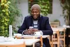 Handsome young man using his mobile phone in the cafe. Portrait of handsome young man using his mobile phone in the cafe Stock Photos