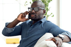 Handsome young man using his mobile phone at home. Stock Photos
