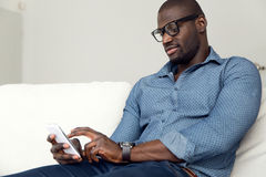 Handsome young man using his mobile phone at home. Royalty Free Stock Image