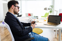Handsome young man using his mobile phone in the office. stock images