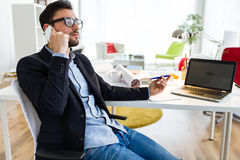Handsome young man using his mobile phone in the office. stock image