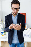 Handsome young man using his mobile phone in the office. royalty free stock image