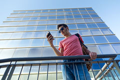 Handsome young man using his mobile phone in the street. Royalty Free Stock Image